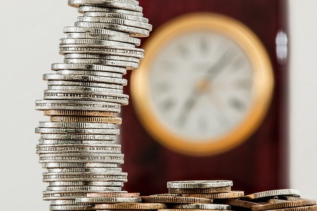 silver and gold coins in front of out of focus clock